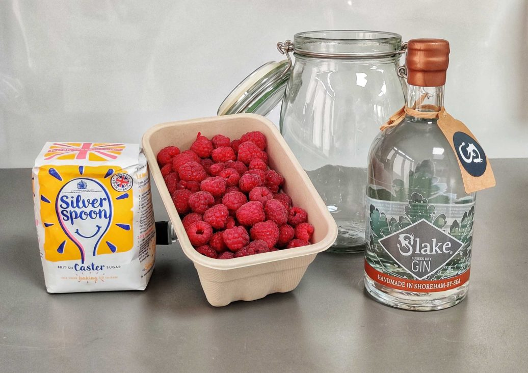 All the ingredients you need to make the best raspberry gin liqueur - caster sugar, fresh raspberries, airtight jar and Slake Sussex Dry Gin